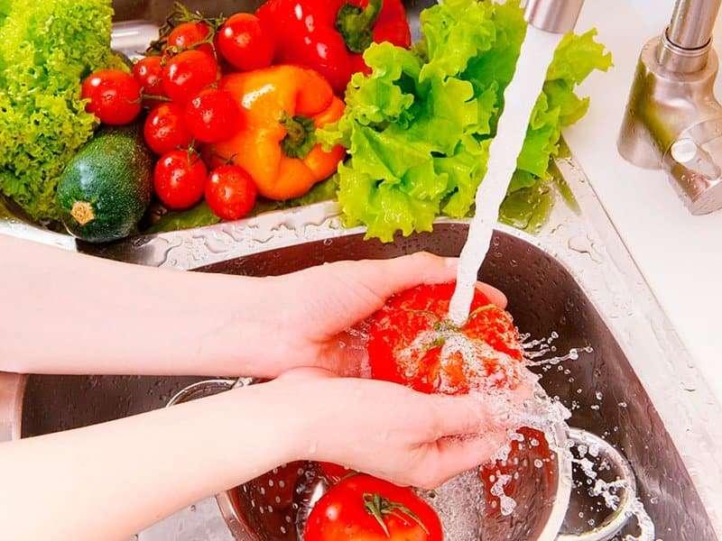 Pessoa Fazendo A Higienização De Alimentos